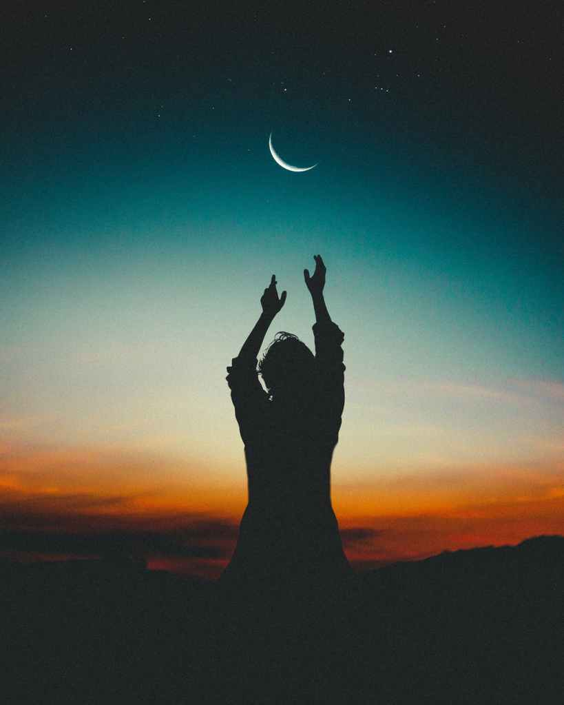 A person reaches out towards the moon, which appears to be just a sliver in the blue and fading sky. It is hard to see the gender of the person, but whoever they are reaches gracefully up and all that can be is a silhouette of the outstretched arms up towards the moon. It is as though they are trying to pull it down or extract lunar energies. The sun is setting and the base of the mountains in front of the person are beginning to be covered with clouds that are already dark. They are being swallowed by a fiery red that breaks into a burnt orange. From there, the last bits of sunlight reach back towards the sky and the horizon fades down to a yellow, almost white. It has a hazy look that won't last long, for night is soon going to push it down. The moon is already bright, with a few stars around it up in the night sky. It is like the sun and moon are meeting each other before they go their own path for the rest of the evening.