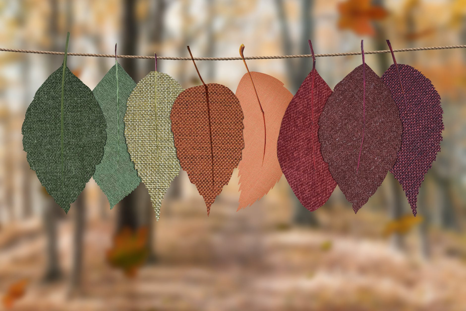Leaves hanging on string with an autumn background. Header for the section talking about Mabon. This holiday is also known as the autunmnal equinox.