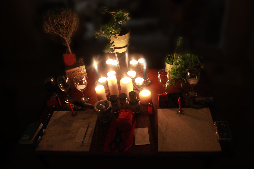 Image of a candle lit pagan altar with plants and chalices.
